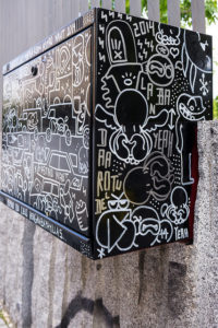 Picture of rectangular black box set on concrete wall or rail, with grafitti mainly in white all over it.