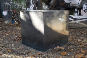 Picture of a large black metal box outside, with fallen leaves scattered around it.